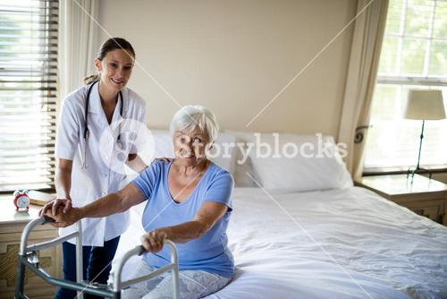 Female doctor helping senior woman to walk with a walker