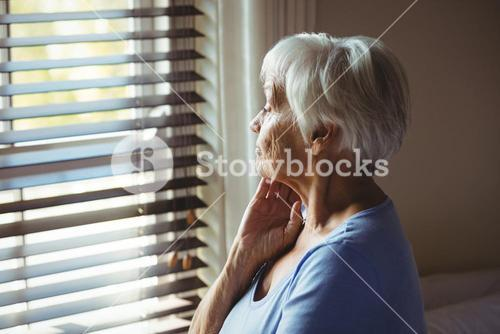 Thoughtful senior woman looking out from window