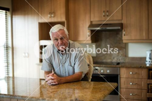Portrait of senior man sitting with hands clasped in the kitchen