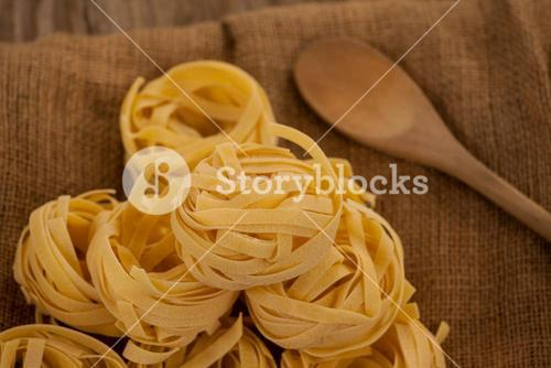 Fettuccine pasta and wooden spoon on sack