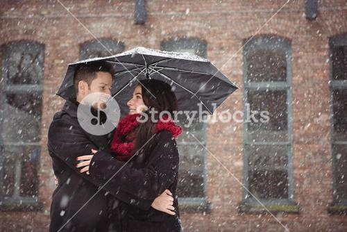 Couple embracing during snowfall
