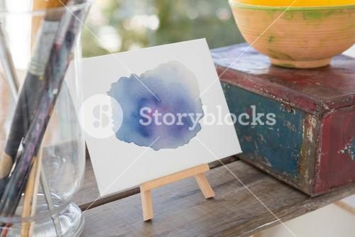Easel with watercolor paint on wooden surface
