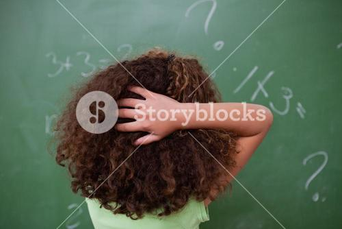 Schoolgirl thinking about algebra while scratching the back of her head