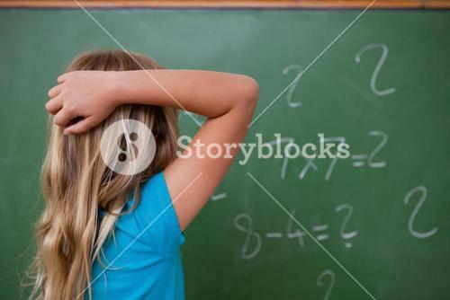 Little schoolgirl thinking while scratching the back of her head