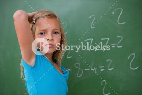 Schoolgirl thinking while scratching the back of her head