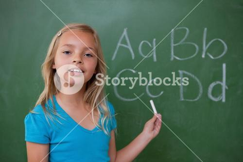 Smiling schoolgirl showing letters
