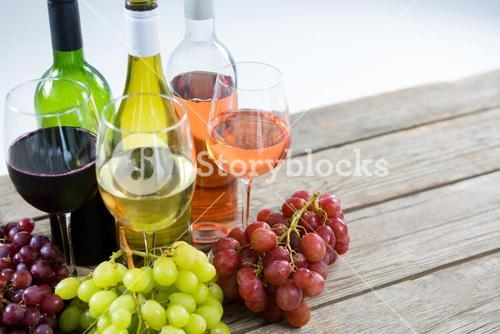 Bunches of various grapes with wine glass and bottles