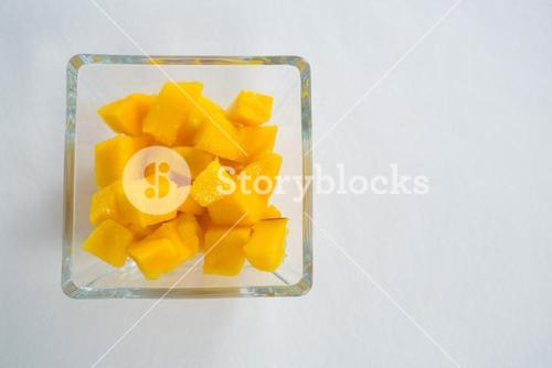 Chopped mangoes in glass bowl