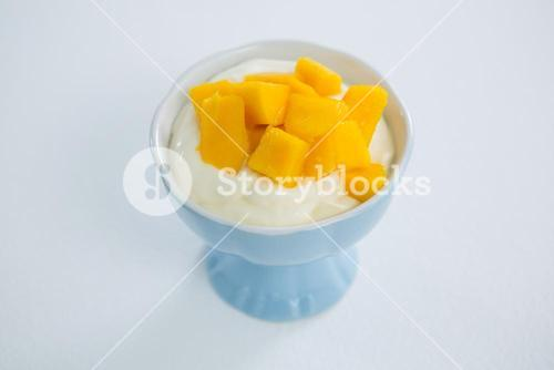 Chopped mangoes with cream in bowl