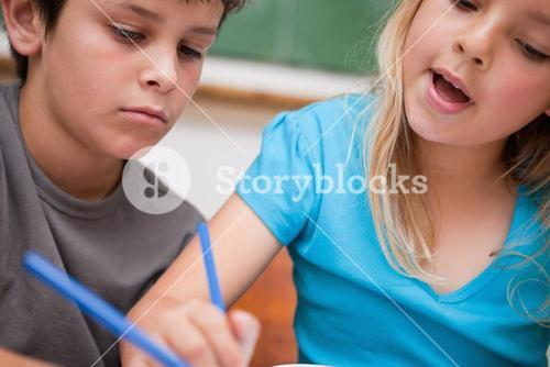 Close up of two children writing