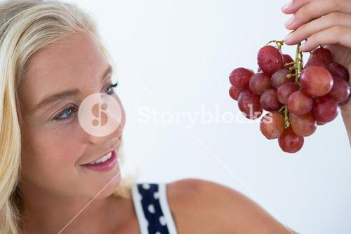 Beautiful woman looking at bunch of red grapes