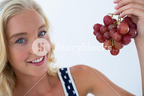 Beautiful woman holding at bunch of red grapes
