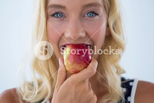 Portrait of beautiful woman eating red apple