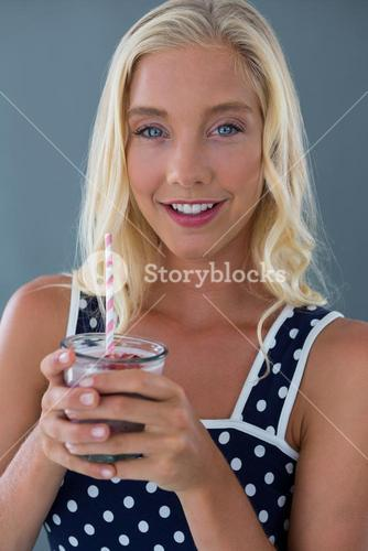 Portrait of beautiful woman holding glass of smoothie