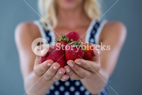 Mid-section of woman holding strawberries