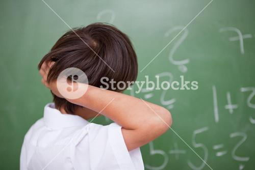 Schoolboy thinking while scratching the back of his head