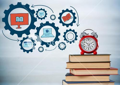 Pile of books and clock with blue gear graphics against blurry grey wood panel