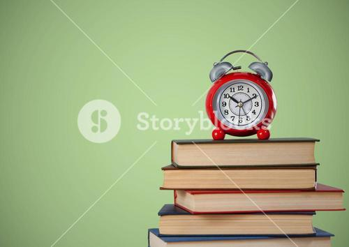 Pile of books and clock against green background