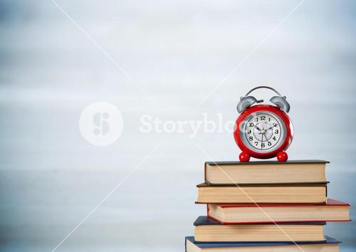 Pile of books and clock against blurry grey wood panel