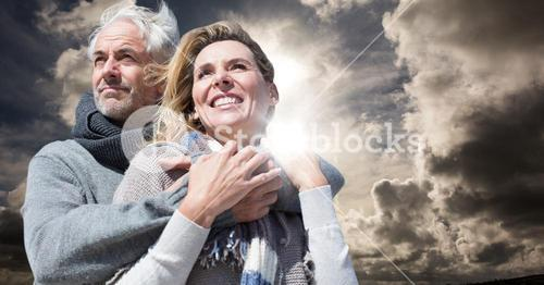 Couple in winter clothes against sky and flare