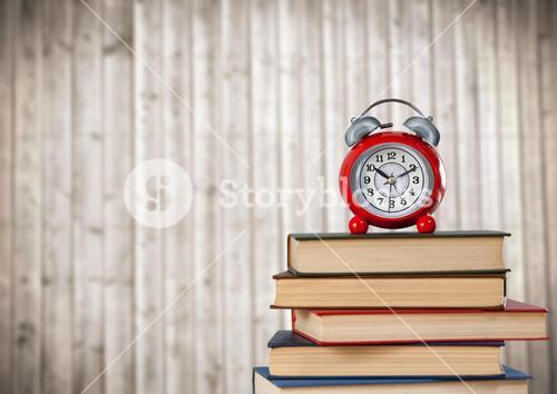 Pile of books and clock against blurry wood panel