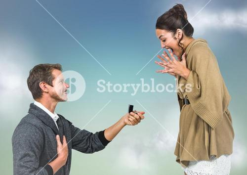 Man propsing to woman against blue green background with clouds