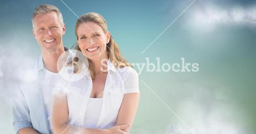 Couple smiling against blue green background with clouds