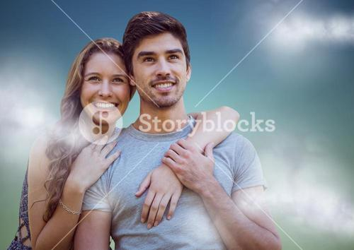Woman with arms around man against blue green background with clouds