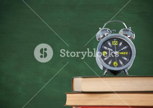 Pile of books with clock against green chalkboard