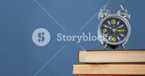 Pile of books with clock against blue background