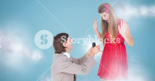 Man proposing to woman against blue background with clouds