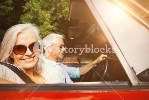 Old couple in a car smiling at camera
