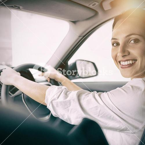 Woman holding steering wheel and smiling at camera