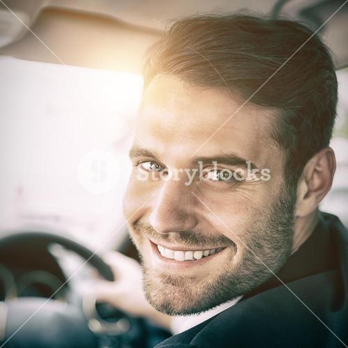 Man sitting in a car and holding a smartphone smiling at camera
