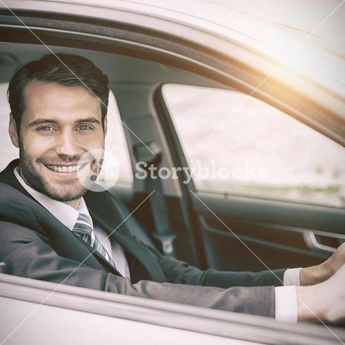 Man sitting in a car smiling and looking at camera