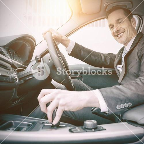 Man driving a car and smiling at camera