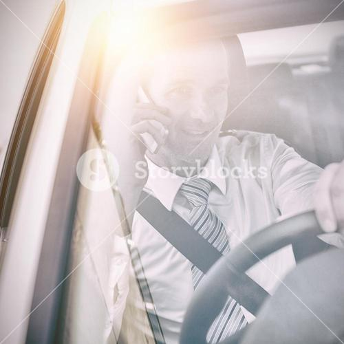Man driving a car and using his phone