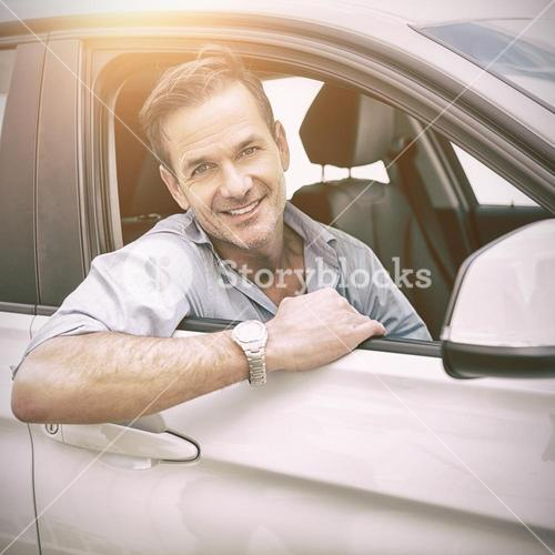 man smiling at camera in a car
