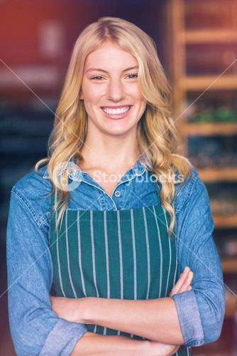 Smiling female staff standing with arms crossed in super market