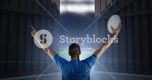 Composite image of rear view of rugby player holding ball with arms raised 3d