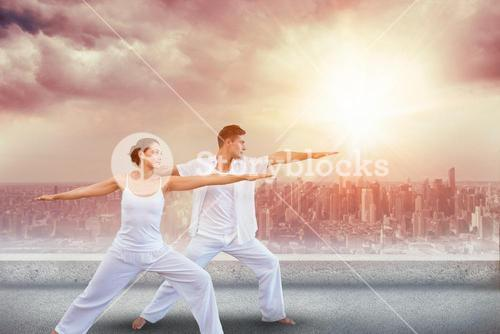 Composite image of peaceful couple in white doing yoga together in warrior position