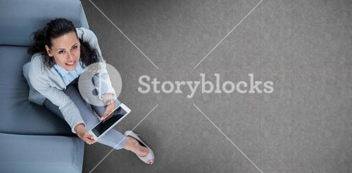 Composite image of woman on her tablet looking up