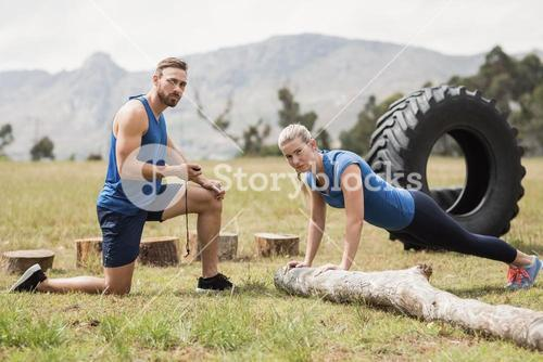 Fit performing pushup exercise while man measuring time