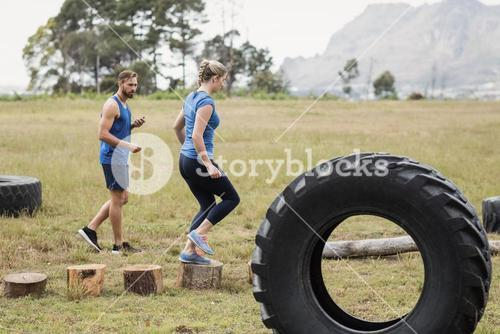 Fit woman running on wooden logs while trainer measuring time