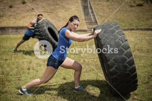 Man and woman flipping a tire during obstacle course