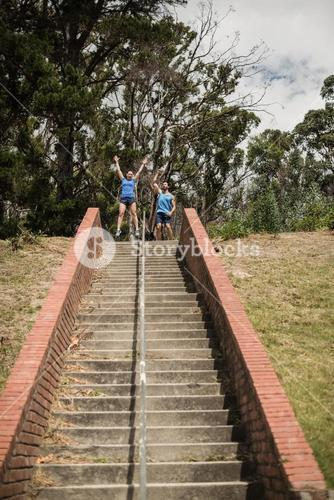 Happy fit man and woman standing near staircase during obstacle course