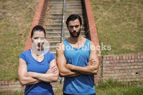 Portrait of fit man and woman standing with arms crossed against staircase