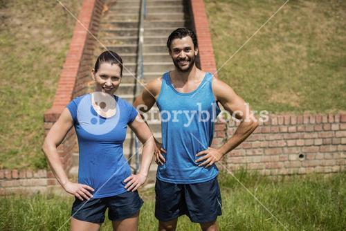 Portrait of fit man and woman standing with hands on hip against staircase