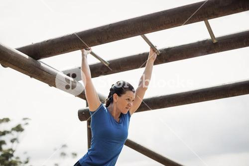 Fit woman climbing monkey bars during obstacle course