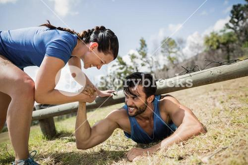 Smiling fit woman helping man crawling under the net during obstacle course